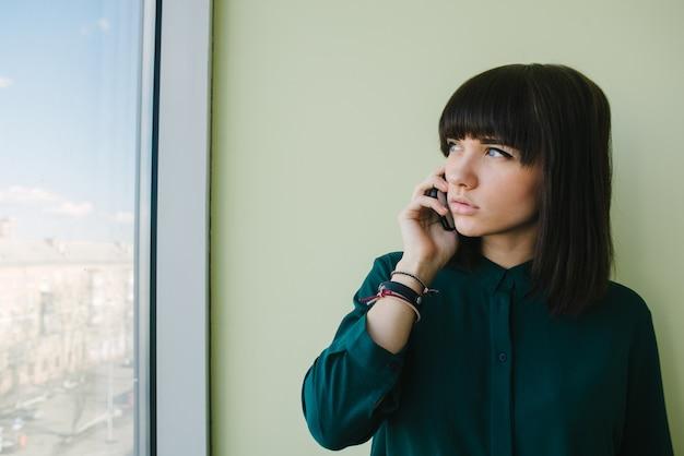Giovane bella donna di impiegato parlando al telefono e guardando nella finestra.
