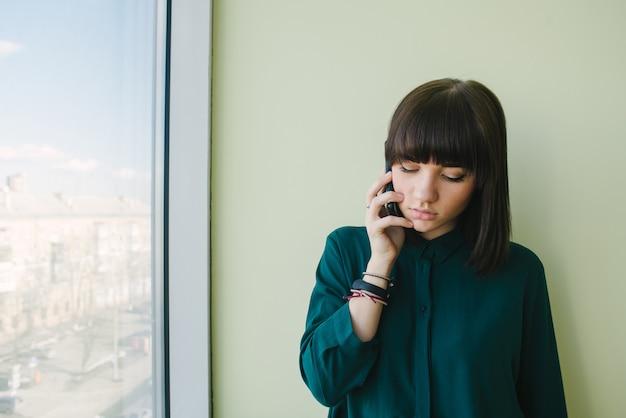 Il giovane bello impiegato di concetto della donna che parla sul telefono alla finestra e guarda giù