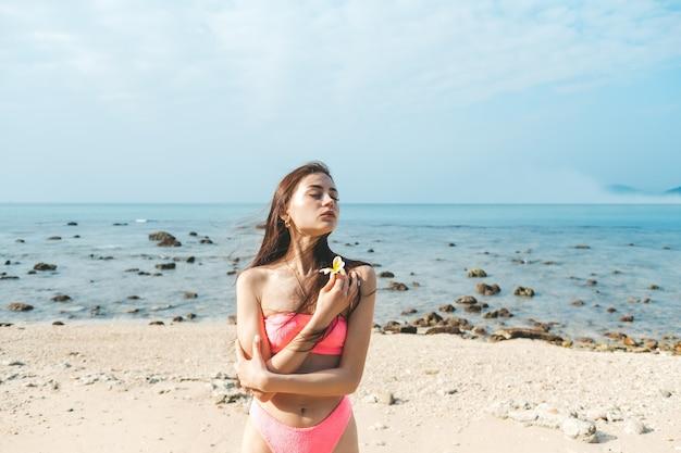 Giovane bella donna in costume da bagno rosa si trova su una spiaggia sabbiosa