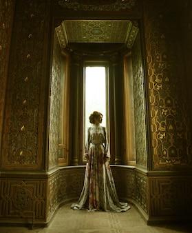 Giovane bella donna in abito rosa in posa in un palazzo di lusso
