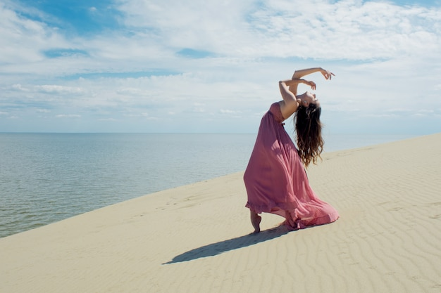 Una giovane donna bellissima in un abito rosa cammina sulle dune di sabbia