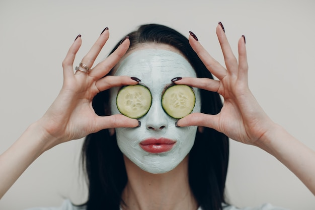 Ritratto di giovane bella donna che riceve maschera facciale all'argilla con cetriolo sugli occhi nel salone di bellezza spa