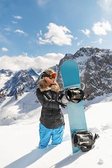 Ritratto di giovane bella donna con lo snowboard sulla stazione invernale