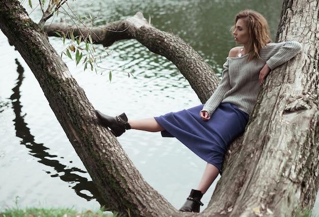 Giovane bella donna in posa su un albero. ritratto di moda glamour. parco d'autunno.