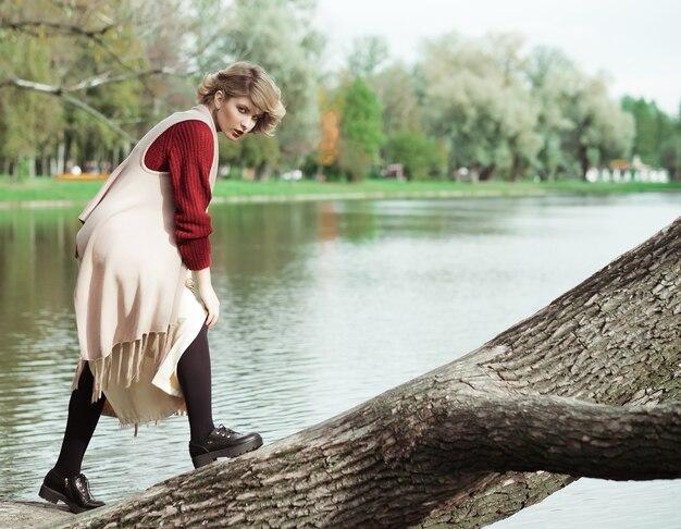 Giovane bella donna in posa su un albero. ritratto di moda glamour.