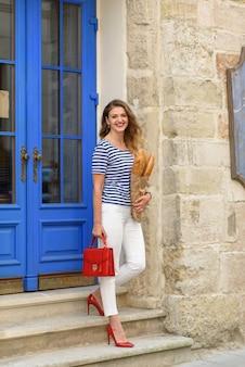 Giovane bella donna in posa con una baguette in mano per le strade della francia.