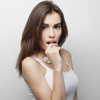 Giovane bella donna in posa con t-shirt bianche, ower sfondo bianco