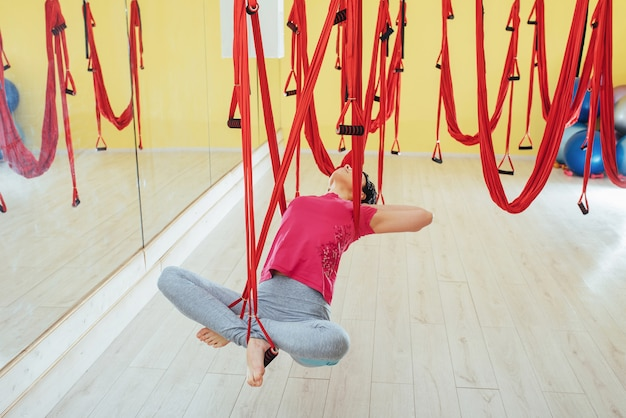 Mosca di pratica di yoga della giovane bella donna con un'amaca in studio.