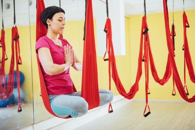 Yoga di pratica della giovane bella donna vola con un'amaca