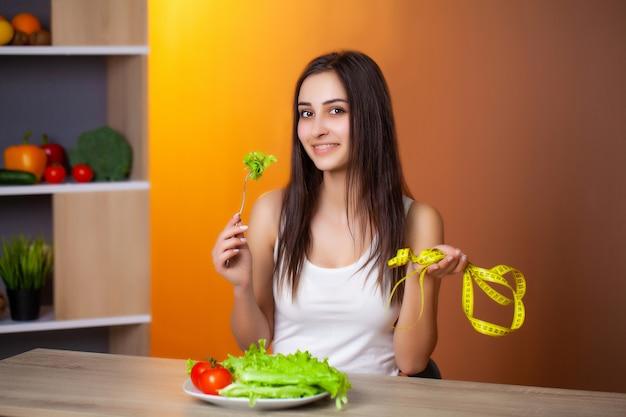 Giovane bella donna che prepara insalata sana di dieta
