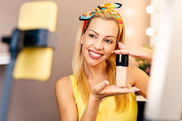 Giovane bella donna e truccatore professionista di bellezza vlogger o blogger che registra tutorial sul trucco da condividere sul sito web o sui social media.