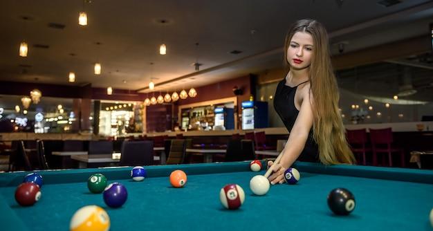 Giovane e bella donna in pub giocando a biliardo