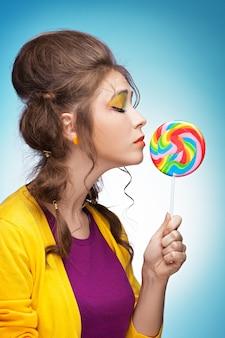 Giovane bella donna che raggiunge per un lecca-lecca colorato