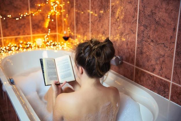 Giovane bella donna che legge un libro e beve vino rosso nella vasca da bagno con schiuma a bolle, decorata con luci colorate, concetto di relax e spa