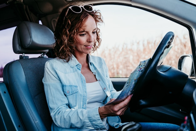 Giovane bella donna che legge una mappa in un'automobile. concetto di viaggio