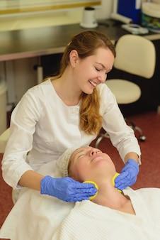 Giovane bella donna che riceve massaggio facciale e trattamento termale nel salone di bellezza