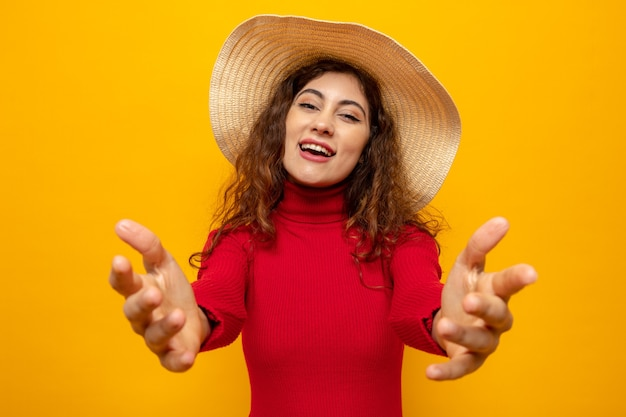 Giovane bella donna in dolcevita rosso con cappello estivo che sembra felice e positivo facendo un gesto di benvenuto con le mani