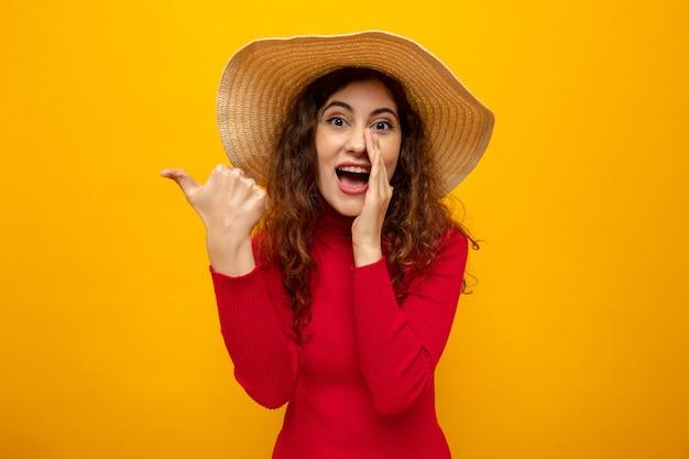Giovane bella donna in dolcevita rosso in cappello estivo che sembra sorridente raccontando un segreto con la mano sulla bocca che punta con il pollice di lato