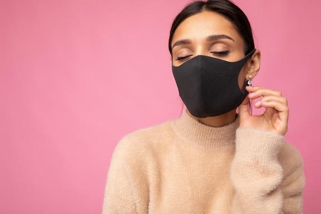 Giovane bella donna in maschera protettiva virus riutilizzabile sul viso contro il coronavirus isolato sulla parete di fondo rosa. spazio vuoto.