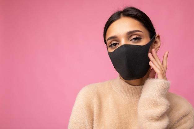 Giovane bella donna in maschera protettiva virus riutilizzabile sul viso contro il coronavirus isolato sulla parete di fondo rosa. spazio libero