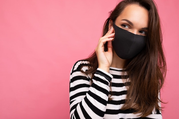 Giovane bella donna in maschera protettiva virus riutilizzabile sul viso contro il coronavirus isolato sulla parete di fondo rosa. spazio libero.