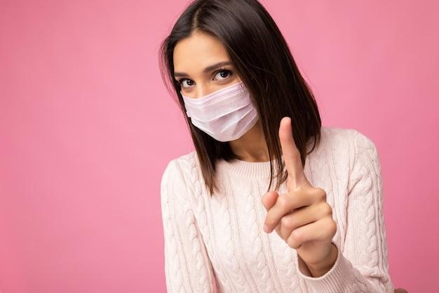 Giovane bella donna con maschera protettiva da virus riutilizzabile sul viso contro il coronavirus isolato sul