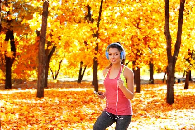 Giovane bella donna che corre nel parco autunnale e ascolta musica con le cuffie.