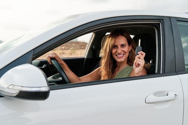 Giovane bella donna che mostra le chiavi della sua nuova auto seduta all'interno. concetto di acquisto o noleggio auto