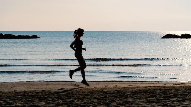 Giovane bello ritratto della siluetta della donna che corre all'aperto sulla spiaggia.