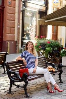 Giovane bella donna si siede su una panchina per le strade della città vecchia.