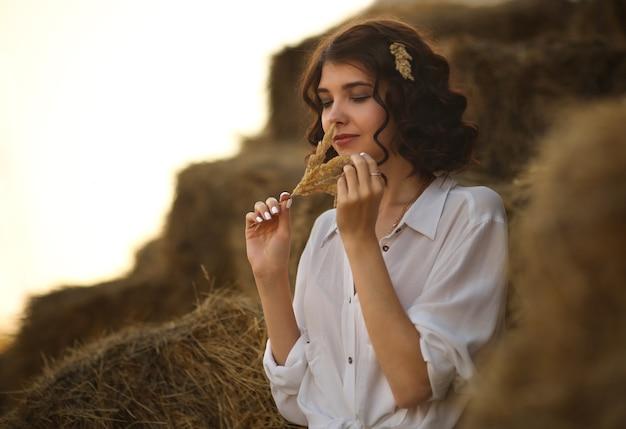 Giovane bella donna si siede che riposa in campagna su una vecchia scala in legno