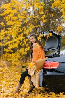 Una giovane bella donna si siede sul bagagliaio di un'auto nella foresta d'autunno