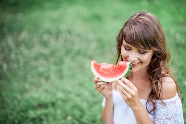 Giovane bella donna che si siede sull'erba e mangia l'anguria. ragazza felice che riposa sull'erba. estati calde. anguria.