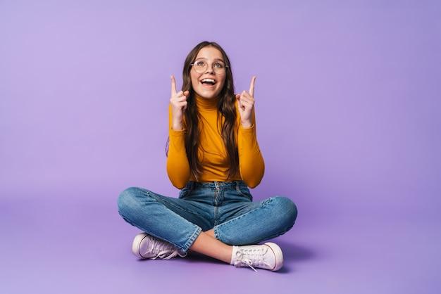 Giovane bella donna seduta con le gambe incrociate e puntando il dito contro copyspace isolato
