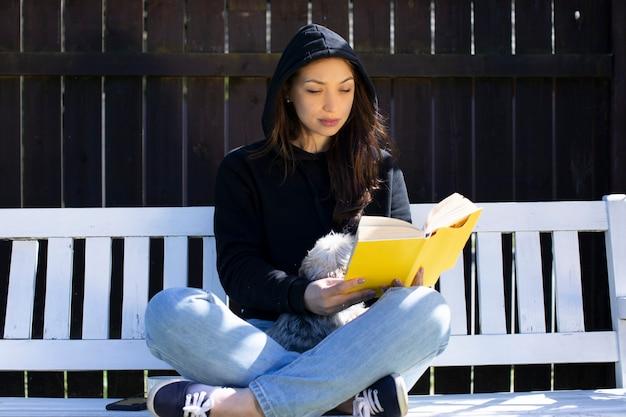 Giovane bella donna seduta con animali domestici su altalena in legno nel cortile della casa di campagna, leggendo un libro