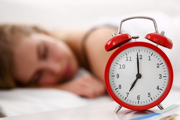 La giovane bella donna dorme bene nel concetto di sveglia del mattino