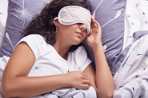 Giovane bella donna che dorme nel letto con la maschera per gli occhi, riposo, relax durante il fine settimana, sdraiato nel letto