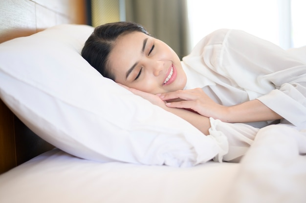 Giovane bella donna che dorme nel suo letto a casa.