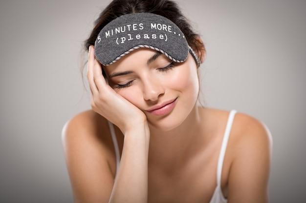 Giovane bella donna che dorme con la maschera per gli occhi