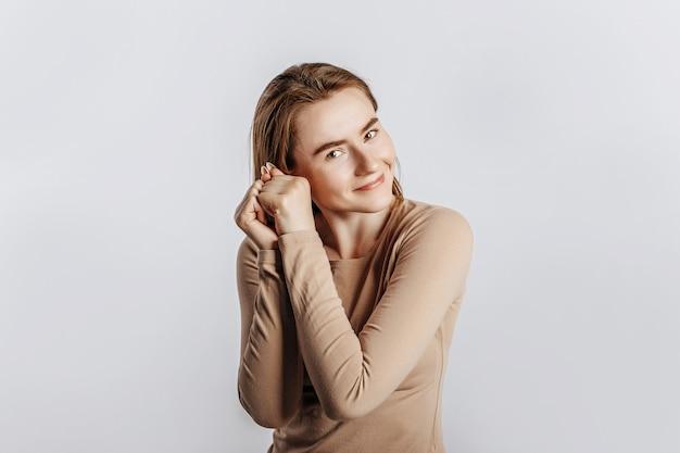 Giovane bella donna sorride e tiene due mani sul viso su un muro bianco isolato