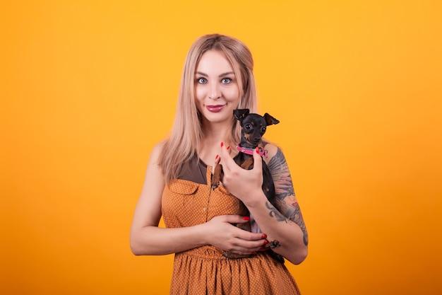 La giovane bella donna sorride e abbraccia il suo cagnolino su sfondo giallo. bella donna. amore per il suo cane, bel vestito.