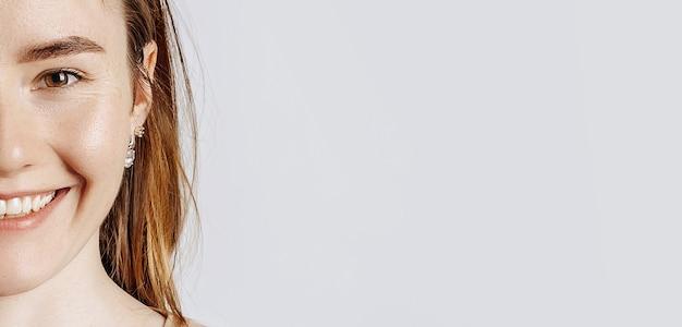 La giovane bella donna sorride su una parete isolata bianca