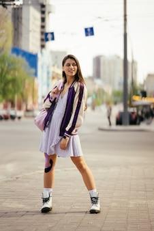 Giovane bella donna che sorride alla telecamera per strada