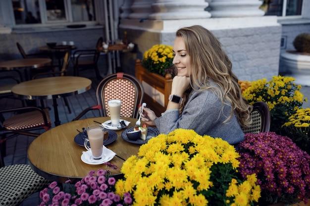 Giovane bella donna sorridente e bere caffè nella caffetteria all'aperto strada