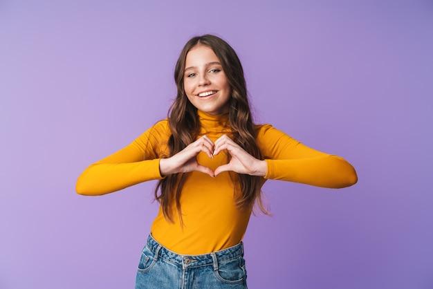 Giovane bella donna sorridente e gesticolando a forma di cuore con le dita isolate