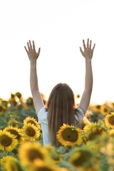 Giovane bella donna sorridente e divertirsi in un campo di girasoli in una bella giornata estiva con le braccia alzate.