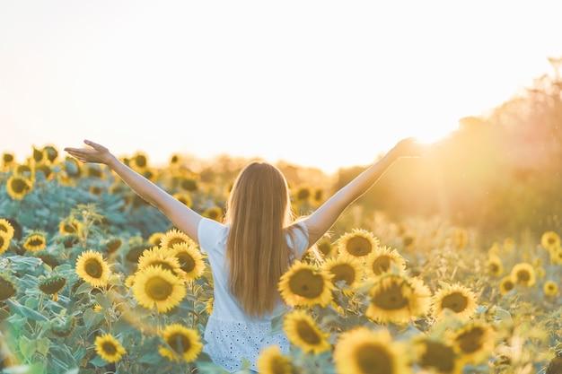 Giovane bella donna sorridente e divertirsi in un campo di girasoli in una bella giornata estiva.