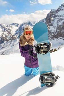 Lo snowboarder della giovane bella donna gode della stazione sciistica. tiro verticale.