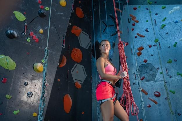 Giovane bella donna in abbigliamento sportivo e attrezzature per l'alpinismo