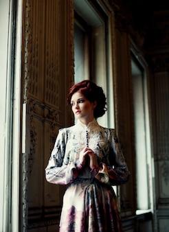 Giovane bella donna in piedi nella stanza del palazzo.